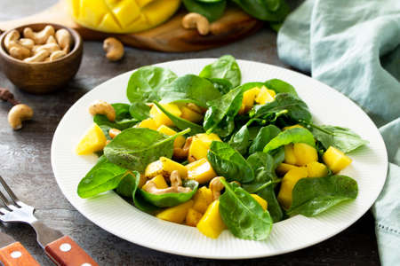 Diet menu, Vegan food concept. Healthy salad with mango, spinach, pecan and vinaigrette dressing on a stone table. Imagens