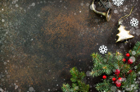 Christmas background frame or greeting xmas card. Christmas tree and decorative ornaments on a dark stone and slate background. Flat lay, top view with copy space.