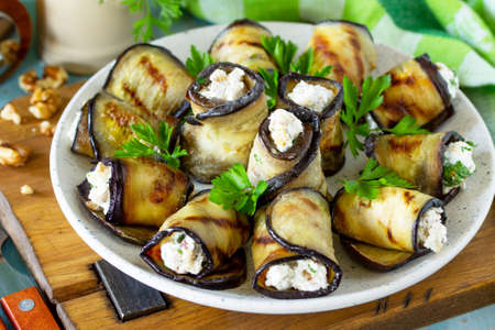 Appetizer stuffed eggplant. Grilled eggplant roll with feta cheese and nuts in a plate on a wooden kitchen table. Stock Photo