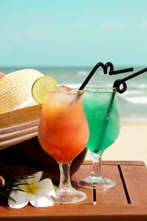 Tropical ice summer drinks and cocktails, towels and a women's straw hat on a white sandy beach on a background of blue sea.