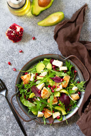 Salad with grilled chicken, avocado, brie cheese, arugula and pomegranate with vinaigrette dressing.