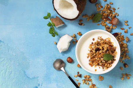 Homemade healthy breakfast. Bowl with homemade baked coconut granola and greek yogurt on a turquoise stone or concrete table.  Copy space. Zdjęcie Seryjne - 140471091