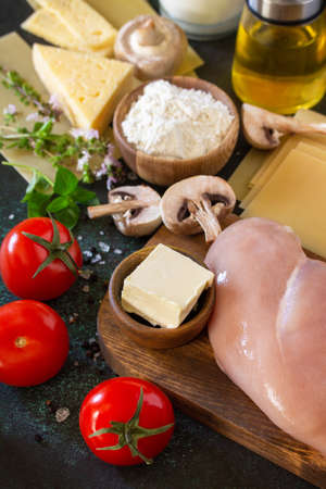 Food background italian. Ingredients for cooking lasagna with chicken and mushrooms on a dark stone background.