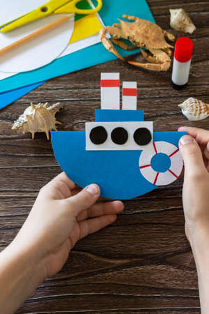 Child holds a paper boat gift for father's day. Children's art project, craft for children. Craft for kids.