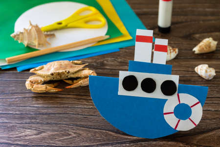 Gift paper boat for father's day on a wooden table. Children's art project, craft for children. Craft for kids.