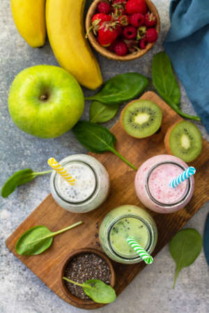 The concept of a healthy diet. Detox smoothies mix. Green smoothies vegetable and fruit smoothies on a stone concrete worktop. Top view flat lay background. Zdjęcie Seryjne