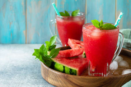 Cold Watermelon Smoothie. Summer Watermelon drink and slices of watermelon on a light stone table. Copy space. Stockfoto