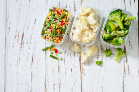 Healthy food is frozen. Stocks of food for the winter. Containers with frozen vegetables. Top view flat lay background. Copy space.