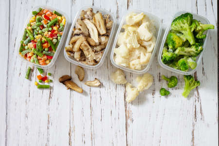 Frozen vegetables. Stocks of food for the winter. Container with frozen vegetables and mushrooms. Top view flat lay background. Copy space.