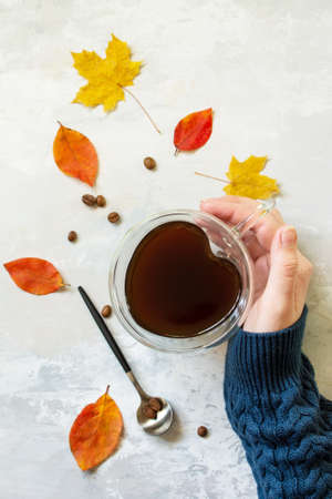 Autumnal concept. A woman is holding a cup of hot coffee. Flat lay top view.