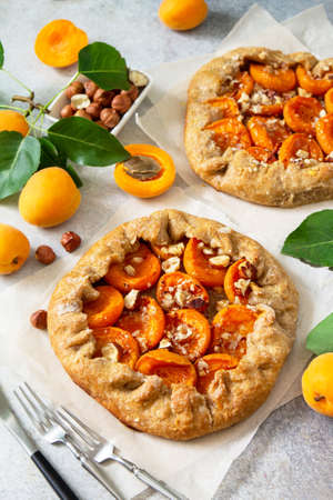Healthy pastries made from rye flour, dessert diet food. Galette with apricots and nuts on a light stone table.