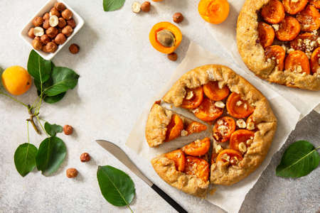 Healthy pastries made from rye flour, dessert diet food. Galette with apricots and nuts on a light stone table. Top view flat lay background. Copy space. Reklamní fotografie