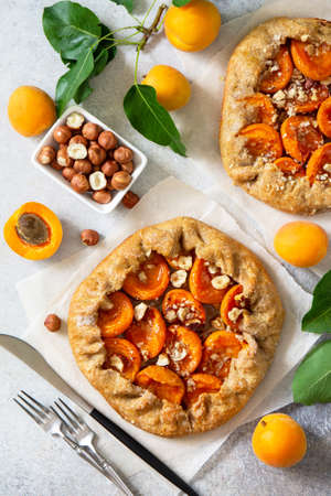 Healthy pastries made from rye flour, dessert diet food. Galette with apricots and nuts on a light stone table. Top view flat lay background.