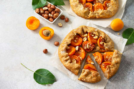 Healthy pastries made from rye flour, dessert diet food. Galette with apricots and nuts on a light stone table. Copy space. Reklamní fotografie