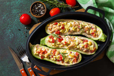 Healthy food. Baked zucchini stuffed with meat and tomatoes in a cast iron pan. Top view flat lay background. Copy space.