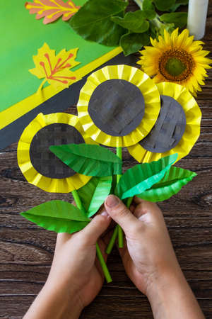 The child holds paper flower sunflower on a wooden table. Childrens art project, handmade, crafts for children. Banco de Imagens