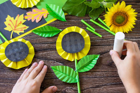 Instructions, step 11. Gift from a paper, sunflower flower on a wooden table. Childrens art project, handmade, crafts for children.