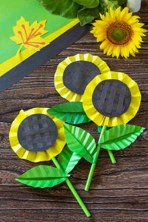 Gift from a paper, sunflower flower on a wooden table. Childrens art project, handmade, crafts for children.