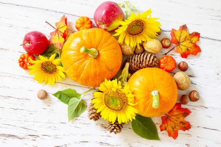 Happy Thanksgiving concept. Pumpkins, sunflowers, apples and fallen leaves on rustic wooden table. Top view flat lay. Stock Photo