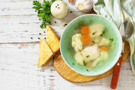 Healthy food concept. Diet turkey soup with vegetables served croutons on a white wooden table. Top view flat lay background. Copy space.