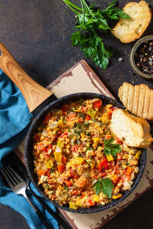 Turkish cuisine. Menemen Scrambled eggs in a cast iron frying pan on a stone countertop. Top view flat lay background. Copy space.