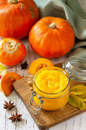 Pumpkin Puree with spices and Pumpkin on a wooden table. Stockfoto