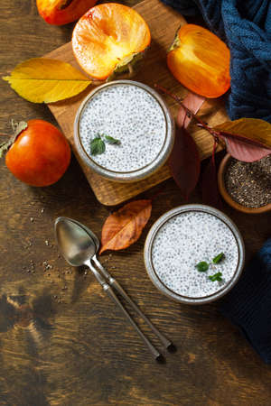 Autumn dessert. Homemade panna cotta with persimmon fruit and chia seeds on a wooden table. Top view flat lay background. Copy space.