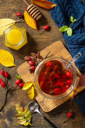 Healthy winter vitamin drink. Hot rosehip tea with honey and dried fruits on a wooden table top. Top view flat lay background. Stockfoto