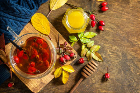 Healthy winter vitamin drink. Hot rosehip tea with honey and dried fruits on a wooden table top. Top view flat lay background. Copy space.