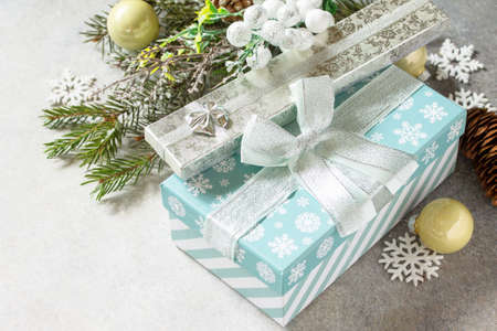 Xmas background. Christmas presents gift blue box and tree branch decor.