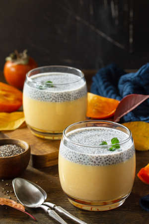 Autumn dessert. Homemade panna cotta with persimmon fruit and chia seeds on a wooden table. Copy space.