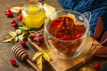Healthy winter vitamin drink. Hot rosehip tea with honey and dried fruits on a wooden table top.