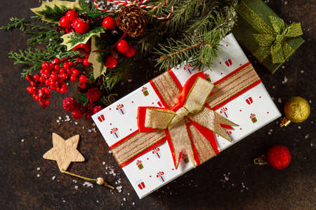 Christmas or New Year concept. Christmas presents gift red box and tree branch decor. Top view flat lay background.