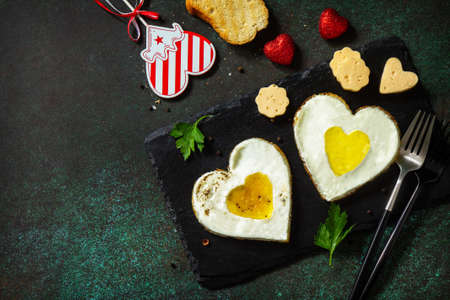 Breakfast on Valentine's Day or brunch. Heart shape fried egg on slate plate. Top view flat lay. Copy space.