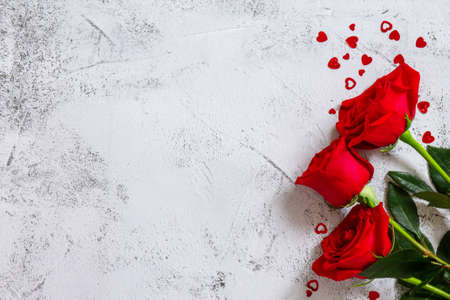 Valentine's Day Concept. Red roses and heart decor on Ultimate Gray background. Space for text or design. Top view flat lay.