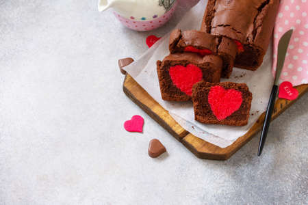 St. Valentine's Day, Mother's Day or Birthday festive dessert. Homemade sweet chocolate brownie with hearts for Valentine's Day on a stone countertop. Copy space.