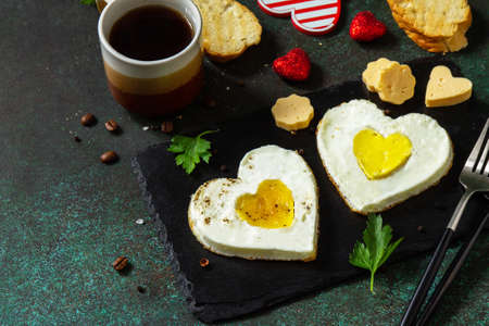 Breakfast on Valentines Day or brunch. Heart shape fried egg on slate plate. Free space for your text.