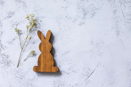 Minimal Easter concept. Wooden bunny on Ultimate Gray Color of the year 2021. Top view flat lay background. Copy space.