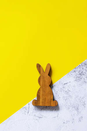 Minimal Easter concept. Wooden bunny on Illuminating Yellow and Ultimate Gray Color of the year 2021. Top view flat lay background. Copy space. Stock fotó