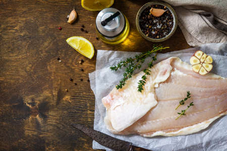 Seafood, raw white fish fillet for cooking. Fresh fillet Pangasius with spices, lemon and thyme on rustic wooden table. Top view, flat lay. Copy space.
