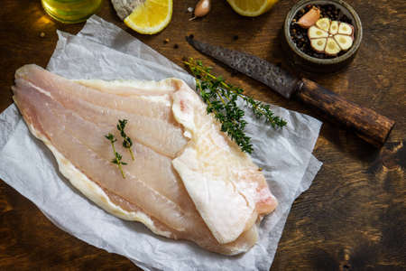 Seafood, raw white fish fillet for cooking. Fresh fillet Pangasius with spices, lemon and thyme on rustic wooden table. Copy space.