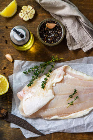 Seafood, raw white fish fillet for cooking. Fresh fillet Pangasius with spices, lemon and thyme on rustic wooden table. Top view, flat lay.
