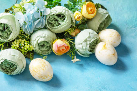 Happy Easter background. Spring flowers and Easter eggs on a concrete blue background. Reklamní fotografie