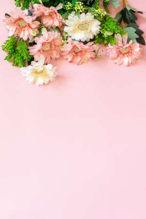 Festive flower arrangement on a pastel pink background. Top view flat lay. Copy space.