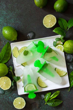 Summer refreshing homemade mojito  with lime juice and mint, mojito fruit ice on a stone countertop. Top view flat lay. Copy space.