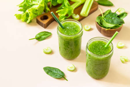 Vegan smoothie recipe. Healthy diet and nutrition, vegan and alkaline drink. Green fresh smoothie with celery and spinach on a pink background. Copy space. Foto de archivo