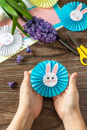 Child is holding an Funny paper easter bunny. Easter handmade Project of children's creativity, handicrafts, crafts for kids. Foto de archivo