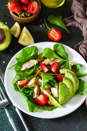 Healthy food, diet lunch menu concept, ketogenic diet and paleodiet. Summer salad with strawberries, grilled chicken and avocado on a stone table.