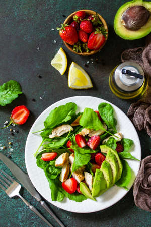 Healthy food, diet lunch menu concept, ketogenic diet and paleodiet. Summer salad with strawberries, grilled chicken and avocado on a stone table. Top view flat lay.