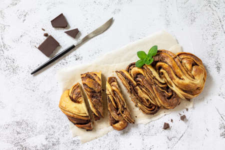 Fresh pastries, chocolate day. Chocolate babka or brioche bread. Sweet yeast dough with chocolate filling and accompanied and nuts. Top view flat lay. 免版税图像
